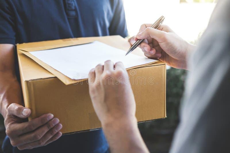 Homem do correio da entrega que dá a caixa do pacote ao formulário do receptor e da assinatura, recibo de assinatura do proprietá fotografia de stock