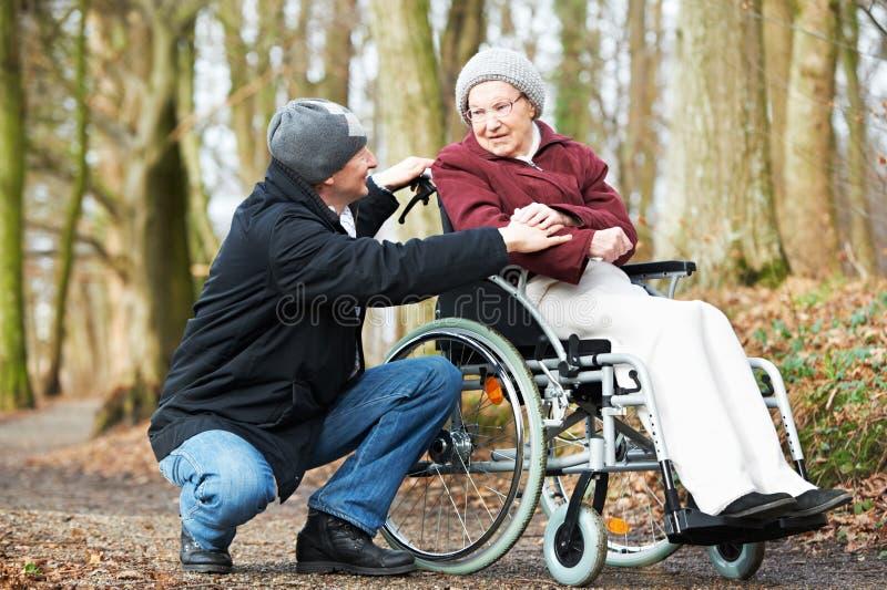 Homem do cuidador que anda com a mulher superior dos enfermos na cadeira de rodas na natureza fotos de stock