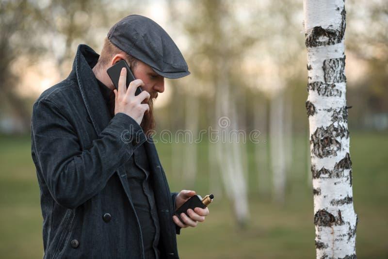 Homem do dispositivo de Vape Retrato exterior de um indivíduo branco brutal novo com grande barba e em um tampão do vintage que v imagens de stock royalty free