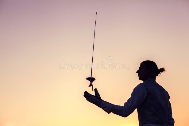 Homem do esgrimista que joga acima sua espada de cerco em um fundo do por do sol foto de stock royalty free