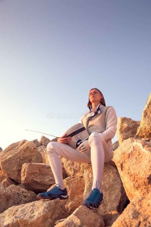 Homem do esgrimista que senta-se sobre a rocha que guarda sua de cerco e uma espada em um fundo do céu azul e vista máscara para  imagens de stock