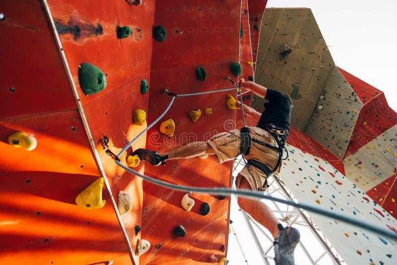 Homem do esporte que pendura a parede de escalada do esporte extremo no gym exterior imagem de stock royalty free