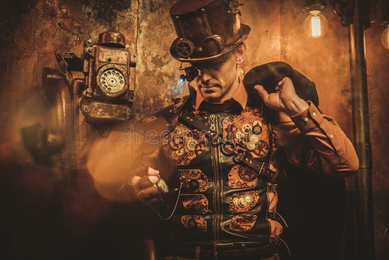Homem do estilo de Steampunk com vários dispositivos mecânicos no fundo do steampunk do vintage fotos de stock