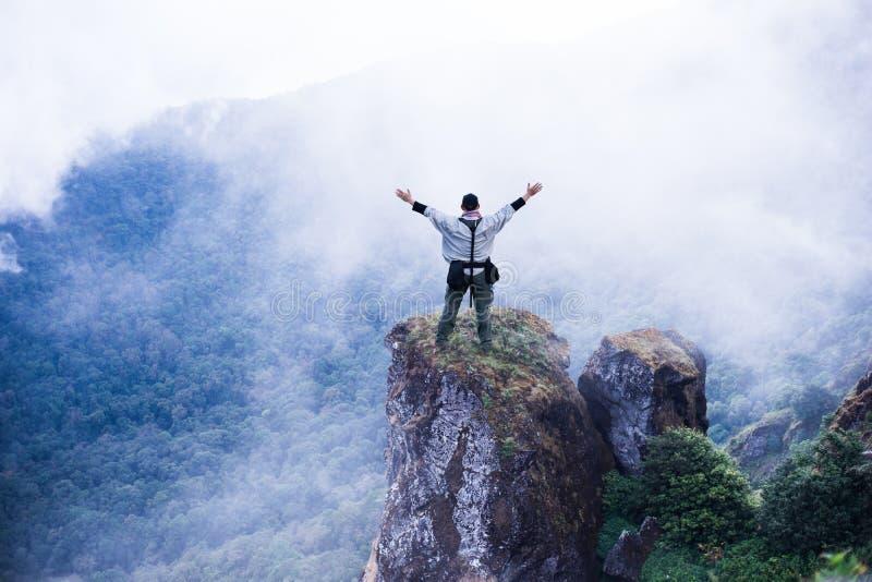 Homem do explorador do turista no auge do fundo da nuvem da montanha imagens de stock