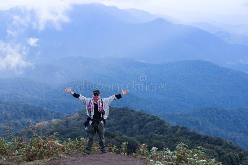 Homem do explorador do turista no auge do fundo da nuvem da montanha fotos de stock royalty free