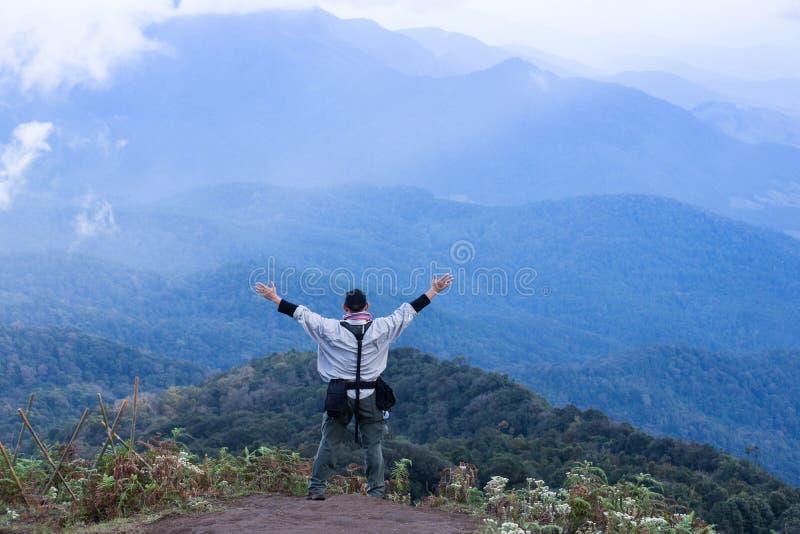 Homem do explorador do turista no auge do fundo da nuvem da montanha fotografia de stock royalty free