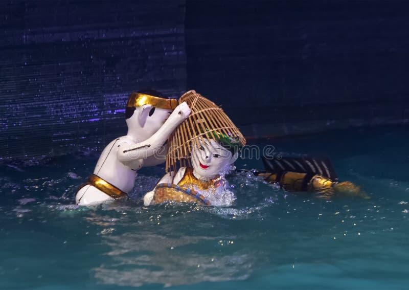 Homem do fantoche da água e mulher com cestas e um peixe do fantoche da água no teatro longo do fantoche da água de Thang, Hanoi, foto de stock royalty free
