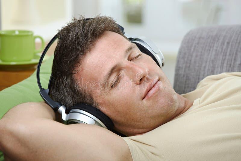 homem do Fechar-olho que escuta o sorriso da música fotos de stock royalty free