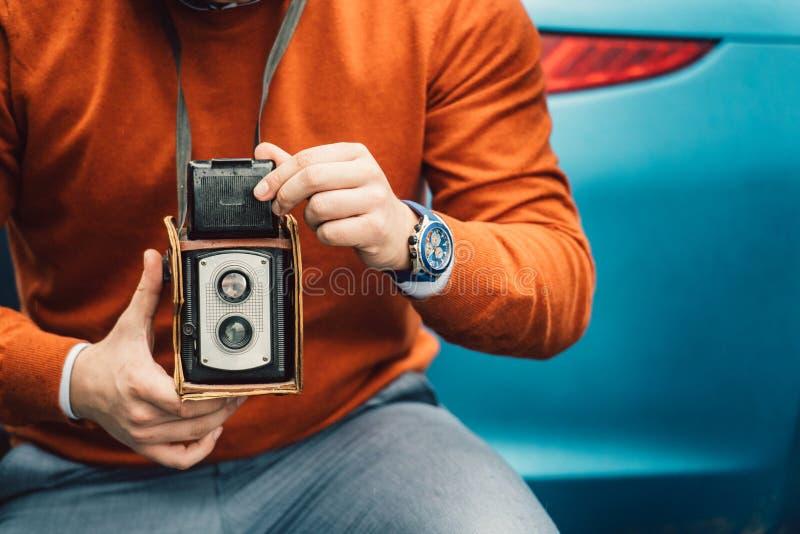 Homem do fotógrafo que toma a foto com a câmera velha do vintage foto de stock royalty free