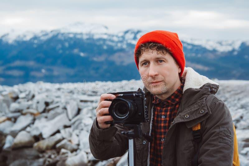 Homem do fot?grafo do viajante do retrato que toma o v?deo da natureza da paisagem da montanha Videographer profissional na avent fotos de stock royalty free