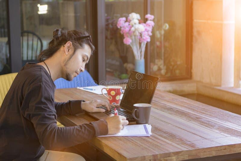 Homem do Freelancer que trabalha com o escritório do portátil do computador em casa imagem de stock
