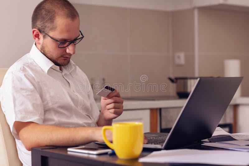 Homem do Freelancer que trabalha da casa e das contas pagando em casa fotografia de stock royalty free