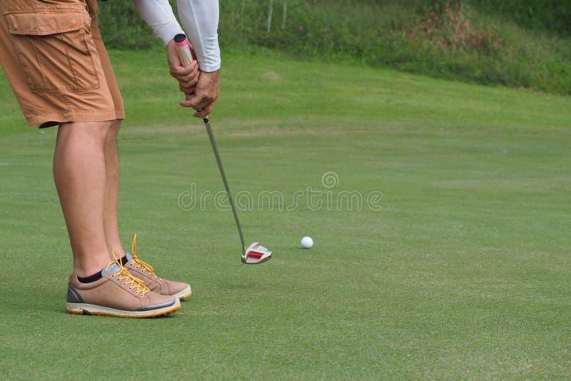 Homem do golfe que põe sobre o gramado verde fotos de stock royalty free