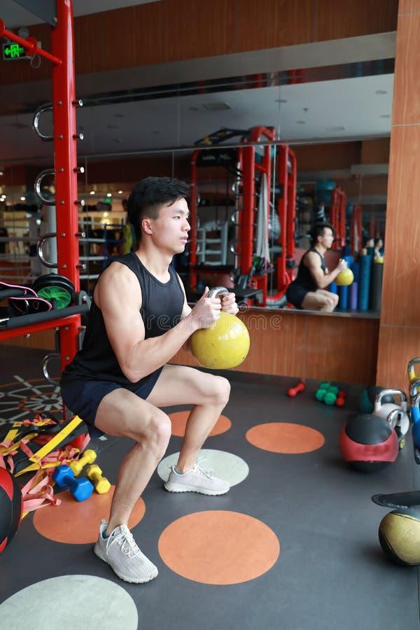 Homem do Gym no gym que dá certo usando os kettlebells internos Bonito, imprensa fotos de stock