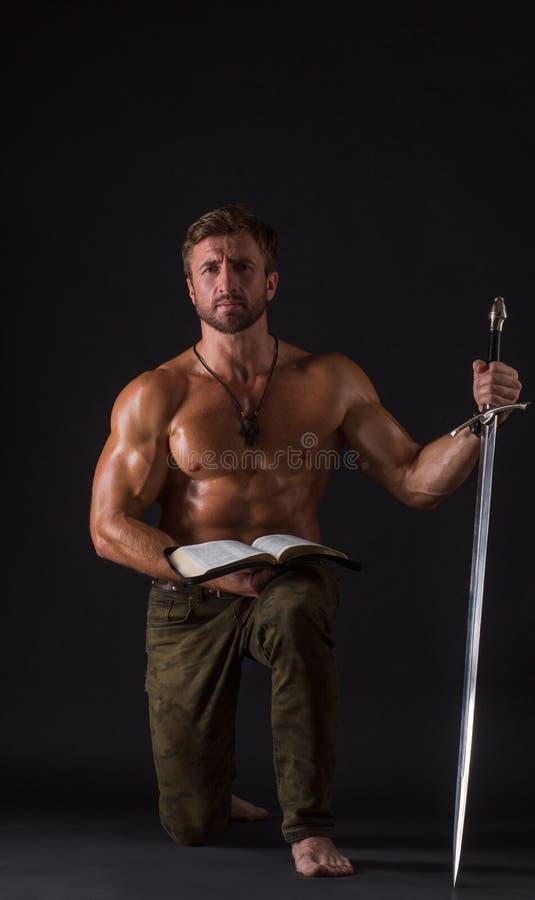 Homem do halterofilista com um livro e uma espada fotos de stock royalty free