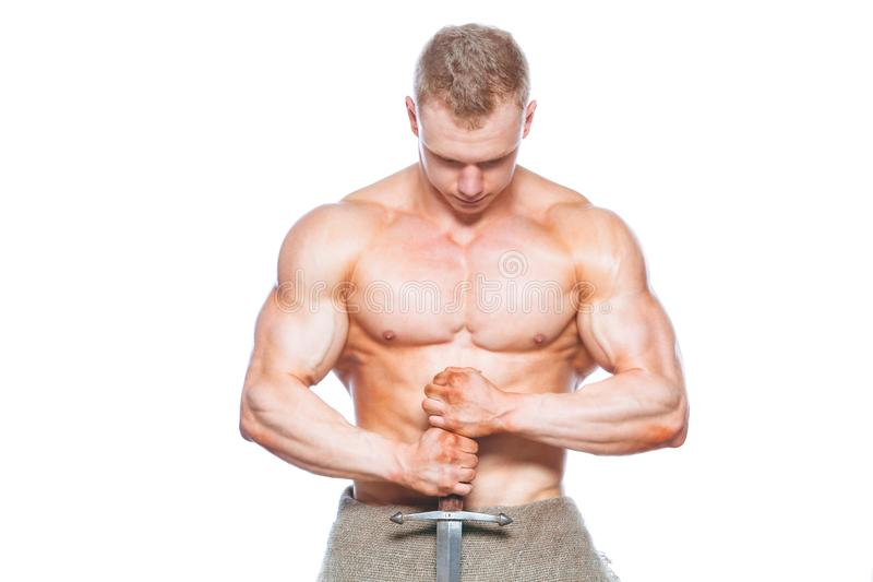 Homem do halterofilista que levanta com uma espada isolada no fundo branco Homem descamisado sério que demonstra seu corpo mascul imagem de stock