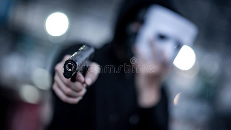 Homem do hoodie do mistério na máscara branca que aponta a arma Conceitos do crime e da violência Foco no injetor fotos de stock royalty free