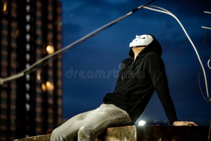 Homem do hoodie do mistério na máscara branca que senta-se no telhado da construção abandonada que olha acima no céu durante o te foto de stock royalty free