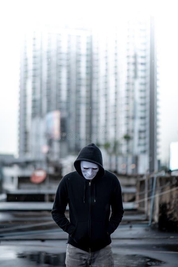 Homem do hoodie do mistério na posição branca da máscara na chuva no telhado da construção abandonada Doença bipolar ou depressiv fotos de stock royalty free