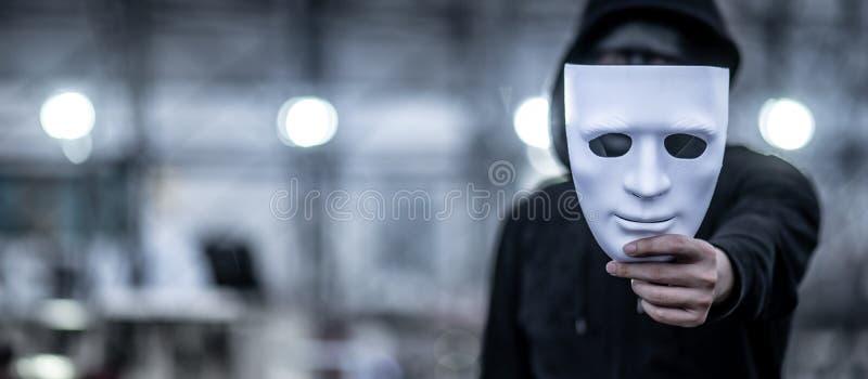 Homem do hoodie do mistério que guarda a máscara branca fotos de stock royalty free
