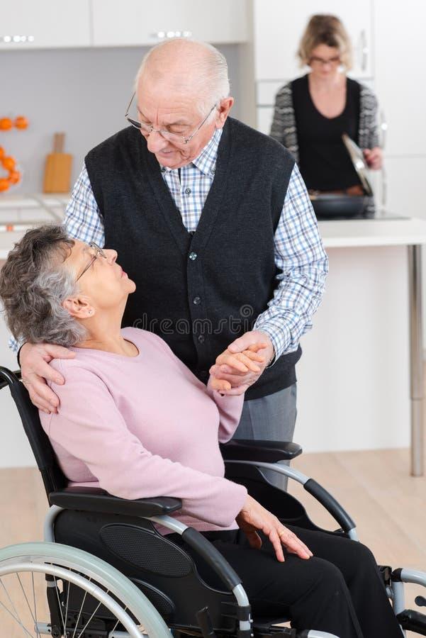 Homem do idoso que fala à esposa na cadeira de rodas fotografia de stock