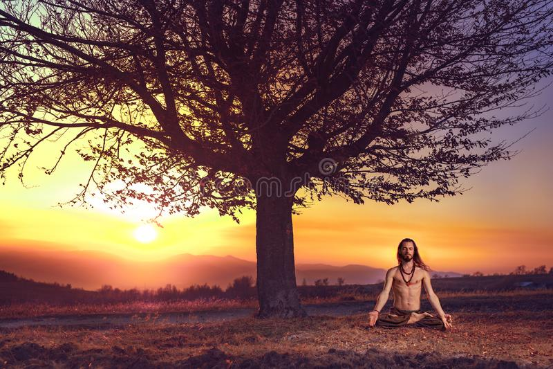Homem do iogue que medita no por do sol nos montes Harmonia emocional da espiritualidade do conceito do abrandamento do estilo de fotos de stock