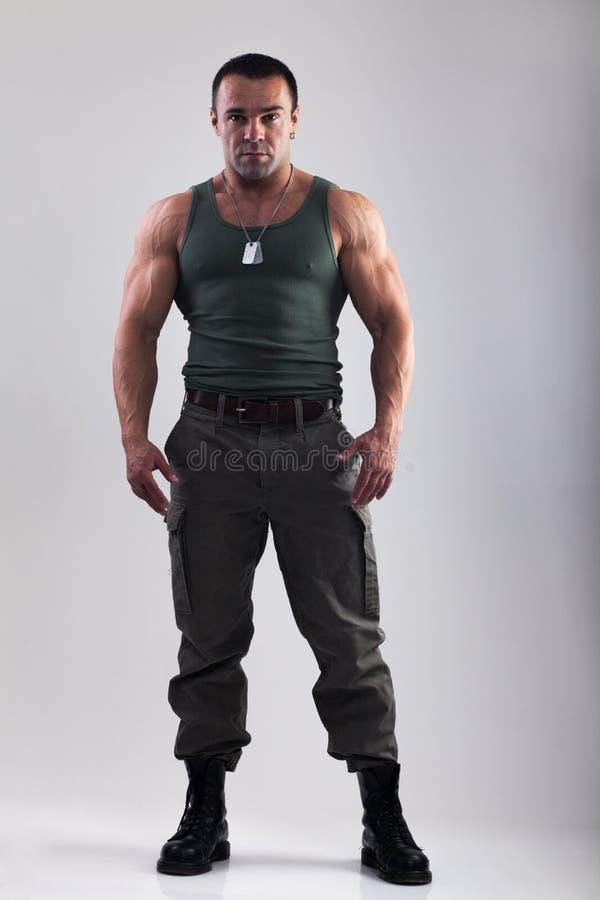 Homem do músculo na roupa militar fotografia de stock
