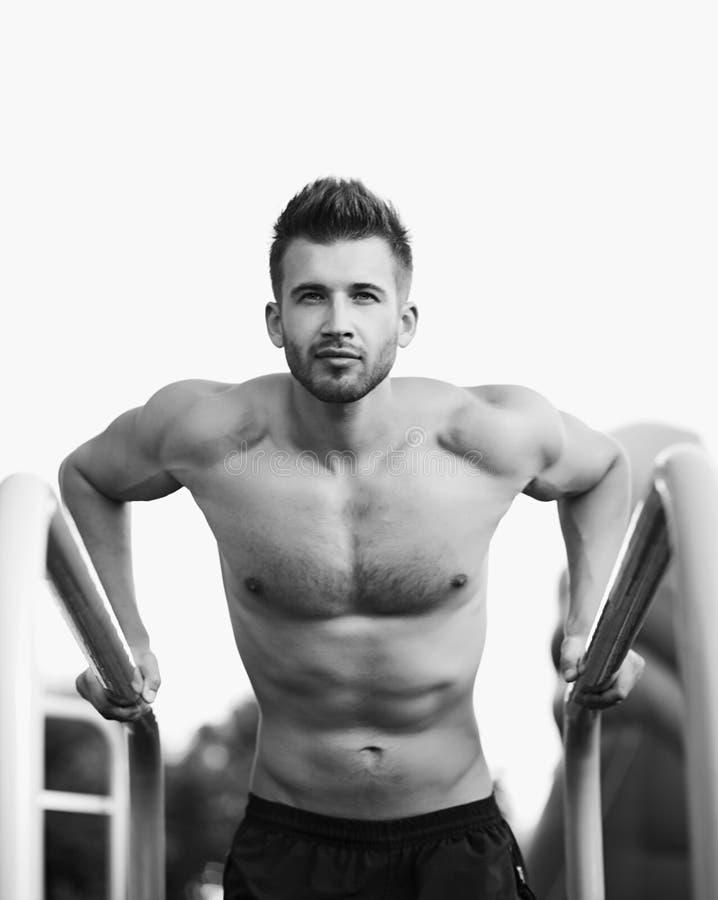 Homem do músculo que faz elevações foto de stock