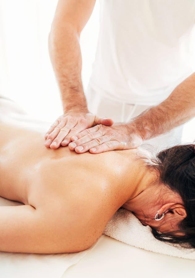 Homem do massagista que faz manipulações da massagem na zona da área da omoplata durante a massagem do corpo fêmea imagem de stock