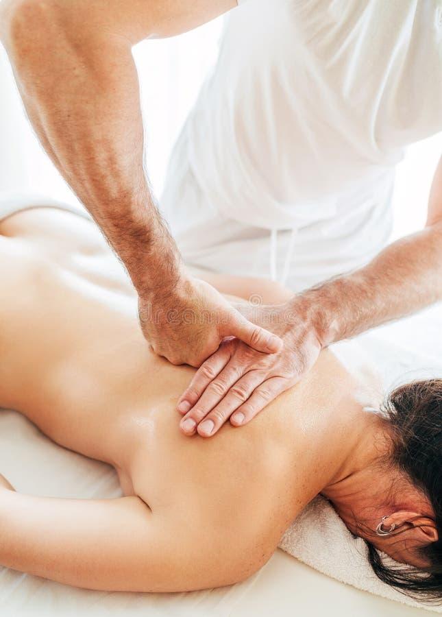 Homem do massagista que faz manipulações da massagem no fim da zona da área da omoplata acima da imagem foto de stock