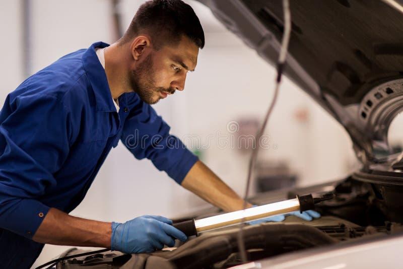 Homem do mecânico com a lâmpada que repara o carro na oficina imagens de stock