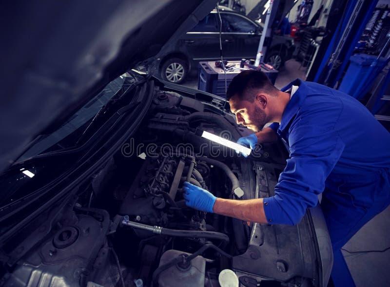 Homem do mecânico com a lâmpada que repara o carro na oficina imagem de stock