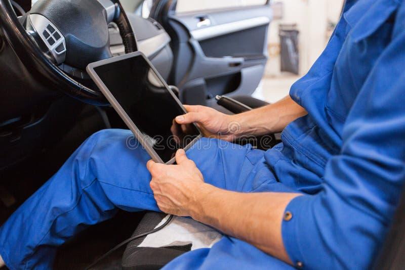 Homem do mecânico com o PC da tabuleta que faz o diagnóstico do carro foto de stock