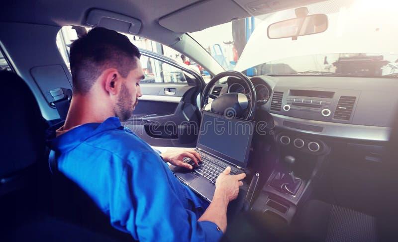 Homem do mecânico com o portátil que faz o diagnóstico do carro imagem de stock