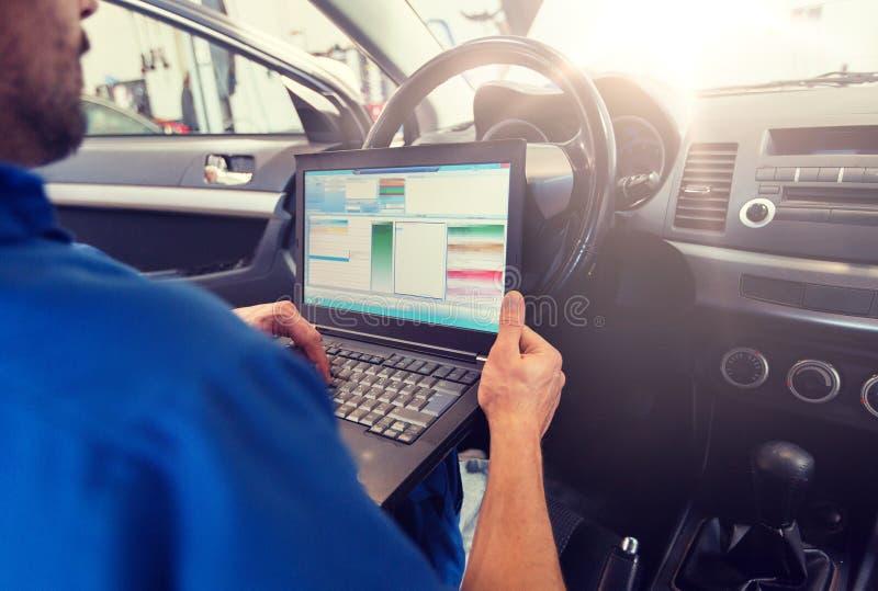 Homem do mecânico com o portátil que faz o diagnóstico do carro fotografia de stock royalty free