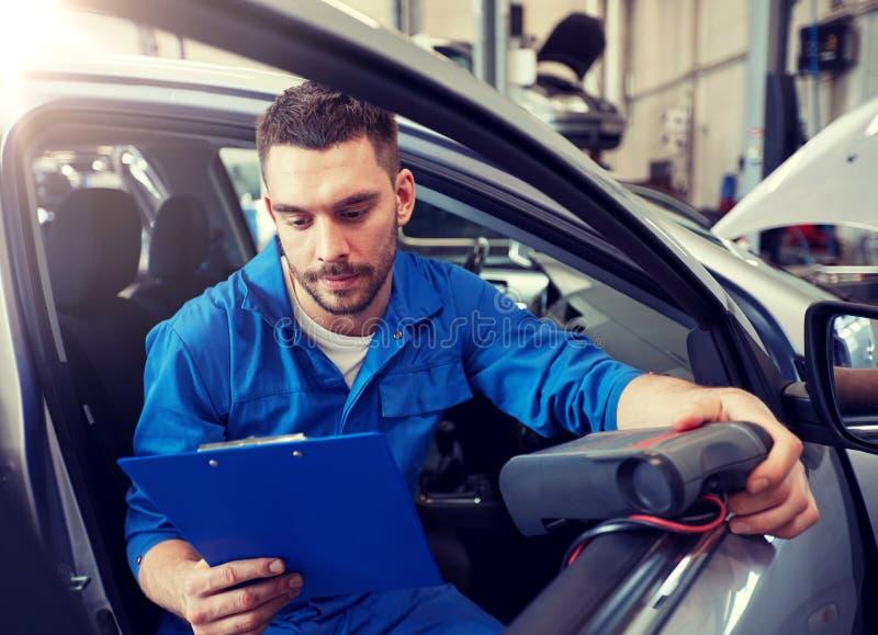 Homem do mecânico com o varredor diagnóstico na loja do carro imagens de stock royalty free