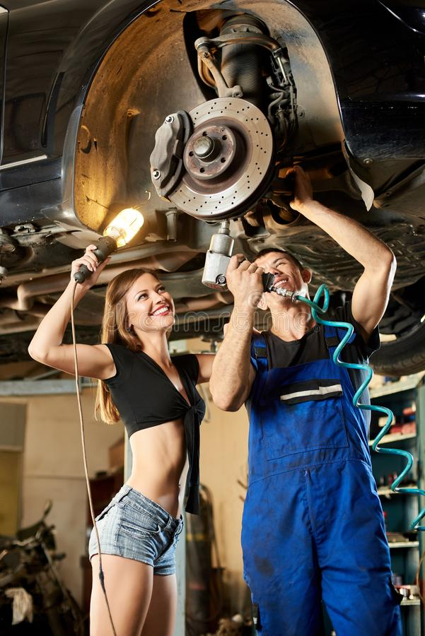Homem do mecânico e mulher 'sexy' que reparam o carro no elevador hidráulico fotos de stock royalty free