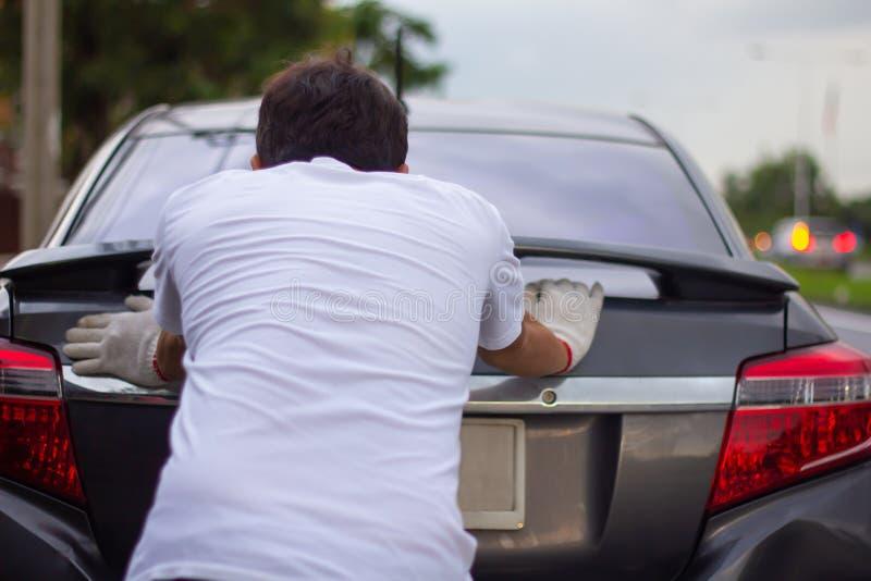 Homem do mecânico que empurra um carro quebrado abaixo da opinião traseira da estrada fotos de stock royalty free