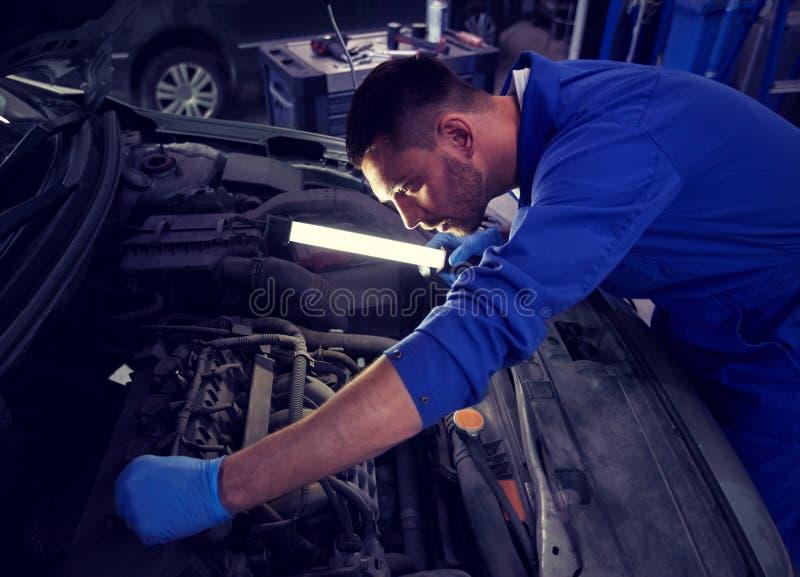 Homem do mec?nico com a l?mpada que repara o carro na oficina imagens de stock royalty free