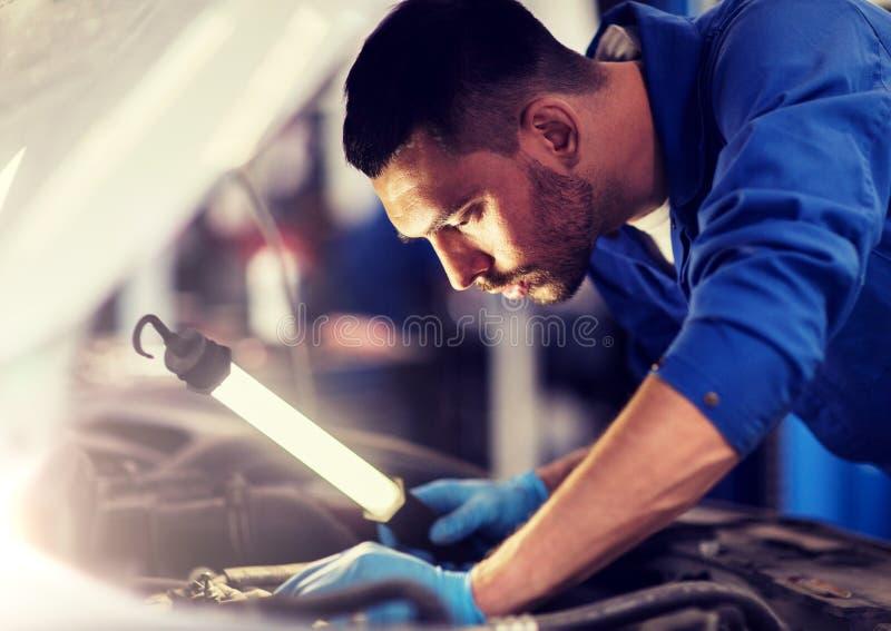 Homem do mec?nico com a l?mpada que repara o carro na oficina fotografia de stock royalty free
