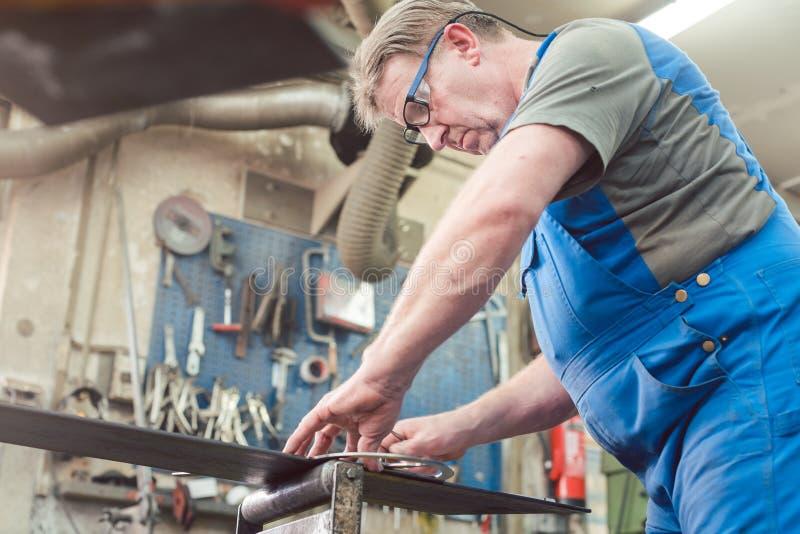 Homem do metalúrgico em sua oficina que trabalha no projeto imagem de stock