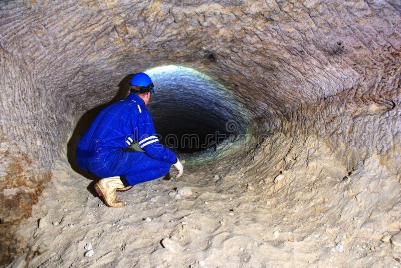 Homem do mineiro subterrâneo em um túnel da mina Trabalhador nos macacões, capacete de segurança fotos de stock royalty free