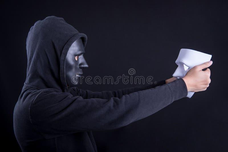 Homem do mistério que guarda e que olha a máscara branca imagem de stock