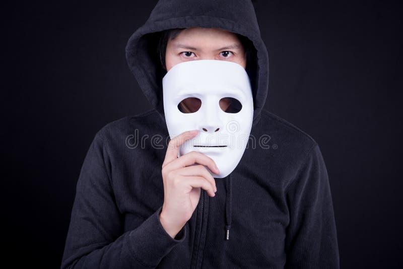 Homem do mistério que guarda a máscara branca para o couro cru sua cara foto de stock royalty free