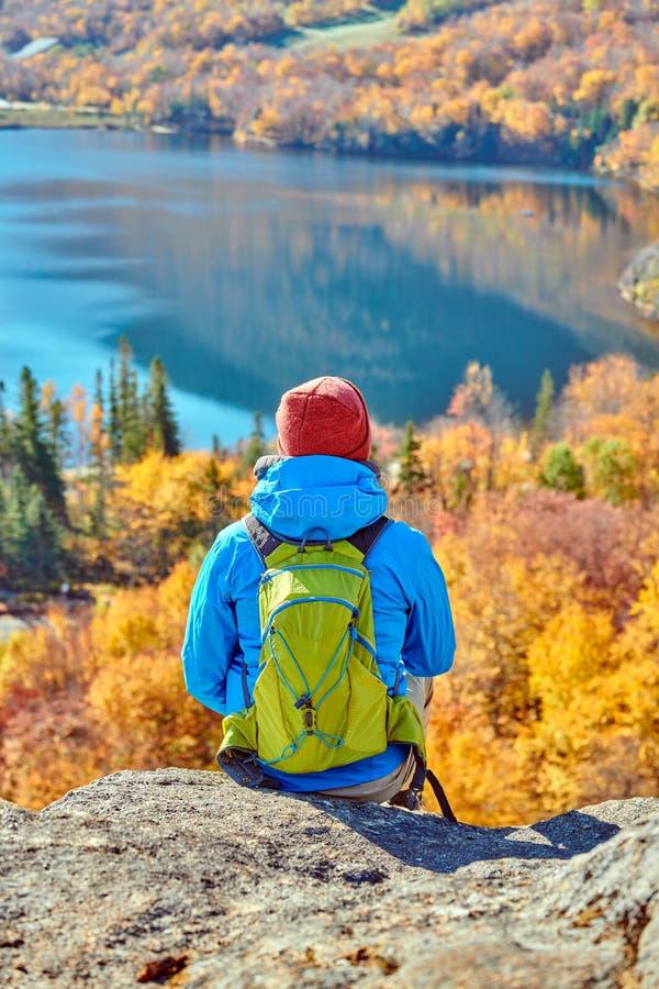 Homem do mochileiro no blefe do artista no outono fotos de stock