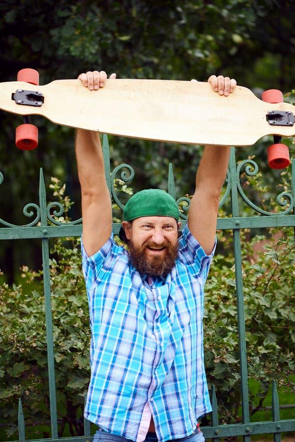 Homem do moderno de Cheetful que levanta com longboard e no tampão verde elegante imagem de stock