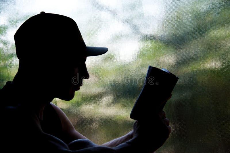 Homem do moderno no tampão que lê o livro Silhueta contra a janela foto de stock royalty free
