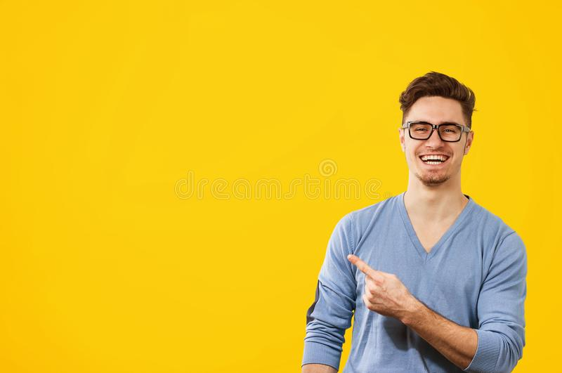 Homem do moderno nos vidros que aponta felizmente afastado no fundo do amarelo alaranjado fotos de stock royalty free