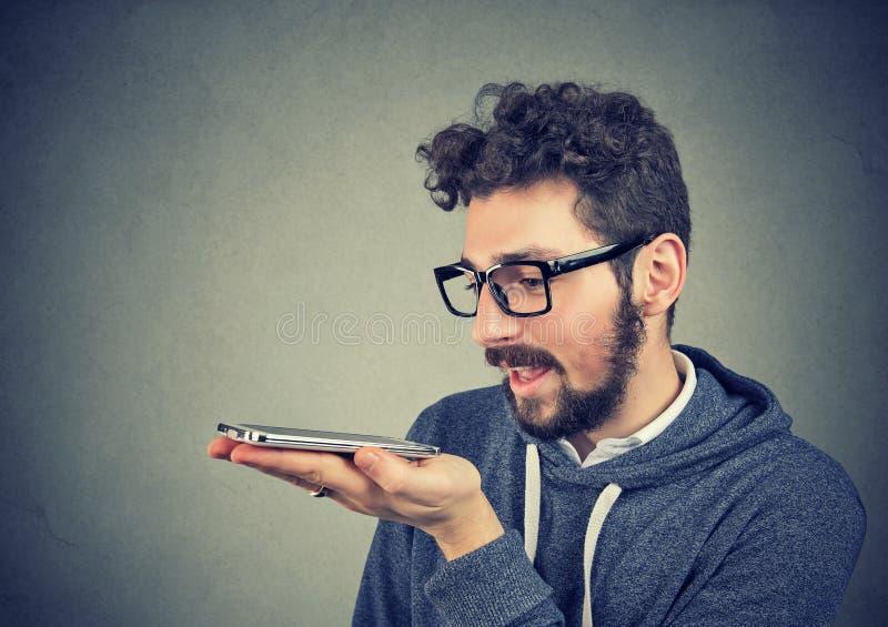 Homem do moderno nos vidros usando uma função esperta do reconhecimento de voz do telefone fotos de stock
