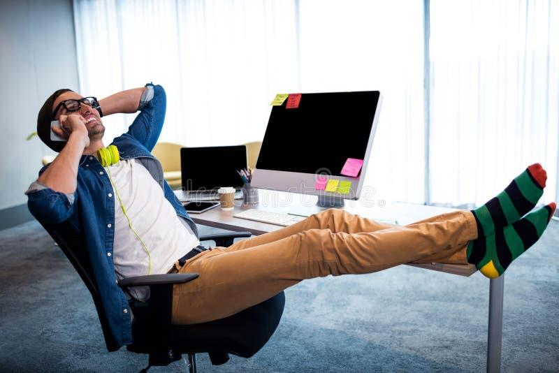 Homem do moderno que chama com smartphone ao relaxar na mesa do computador fotos de stock
